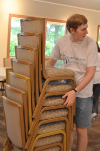 Event Center employee stacking chairs
